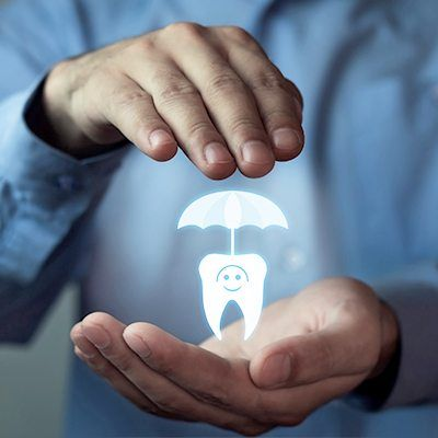 Hands holding an animated tooth and umbrella
